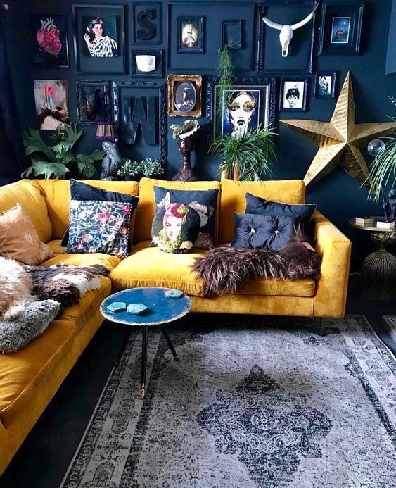 un soggiorno drammatico con un muro di accento blu scuro, un audace muro della galleria, un giallo cuscini componibili e luminosi più una tavola rotonda