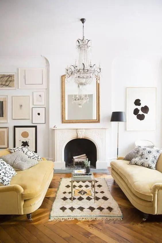 un soggiorno chic con un camino non funzionante, una galleria a parete monocromatica, un lampadario di cristallo e un duo di divani giallo chiaro