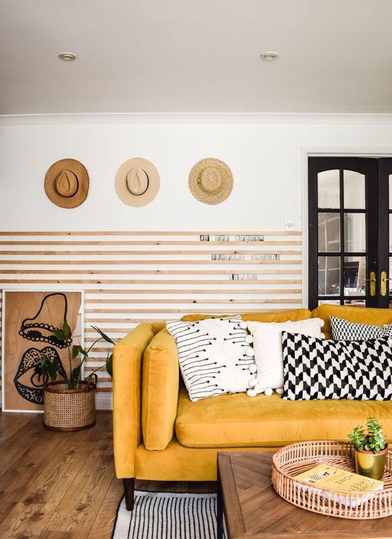 un soggiorno chic con lastre di legno sul muro, un divano giallo e cuscini grafici, cappelli in mostra e alcune piante