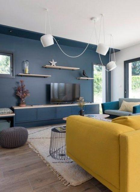 un soggiorno contemporaneo con un muro accento blu marino, un divano giallo, una sedia grigia, lampade a sospensione e mensole sospese è chic