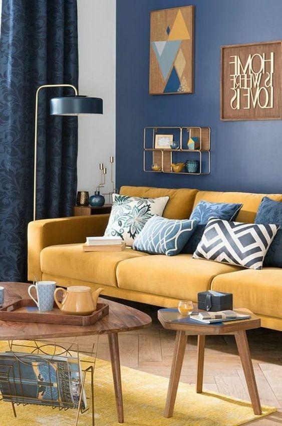 un soggiorno chic con un muro con accento blu scuro, un divano giallo con cuscini blu, un tappeto giallo, una lampada da terra e tavoli in legno