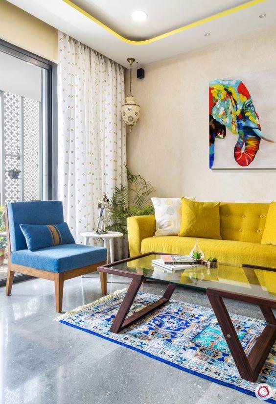 un soggiorno colorato con pareti neutre, un divano giallo, una sedia blu, un tavolo di vetro e un'opera d'arte colorata è sorprendente