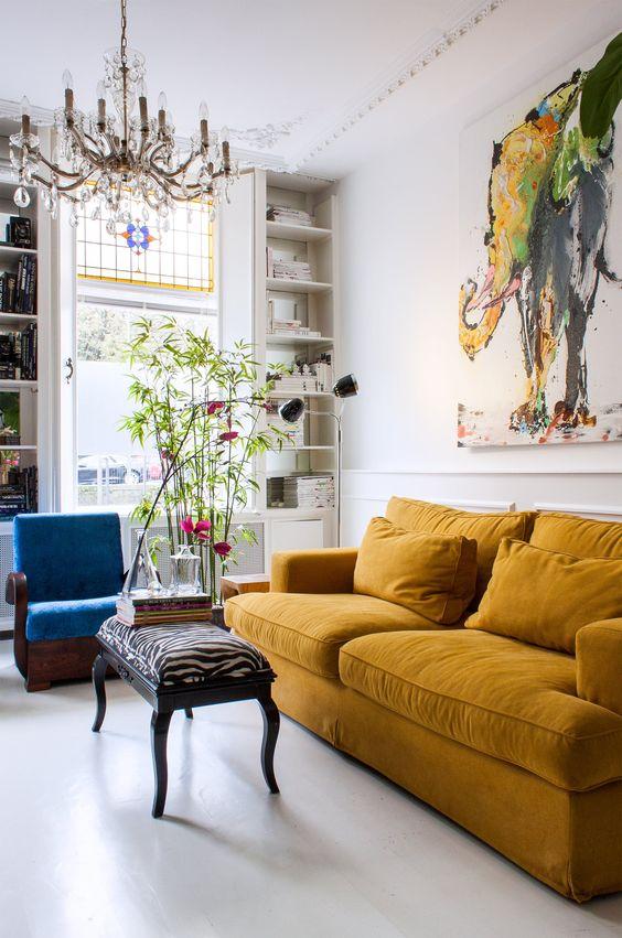 uno splendido soggiorno massimalista con un divano senape, una sedia blu, piante in vaso, un raffinato lampadario e un'opera d'arte audace
