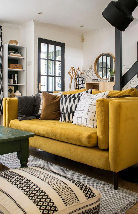 un soggiorno monocromatico con stampe grafiche, un audace divano giallo, un tavolo verde e un fresco scaffale