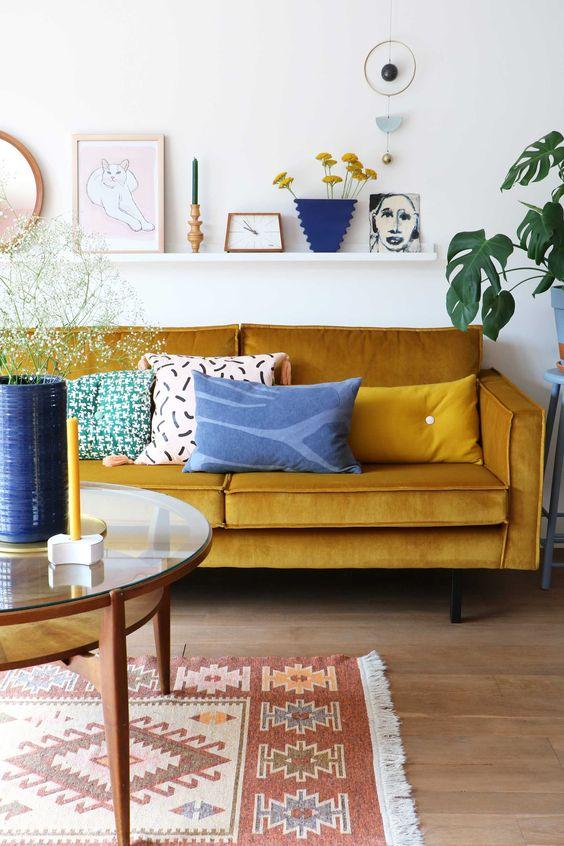 un vivace soggiorno con un divano color senape, un tavolo rotondo, una galleria a sporgenza e tocchi di blu per un contrasto