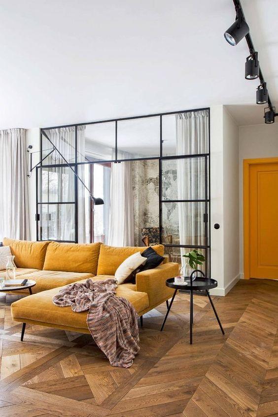 un grazioso spazio contemporaneo con un caldo componibile giallo, un nero in grado e alcuni cuscini bianchi e neri