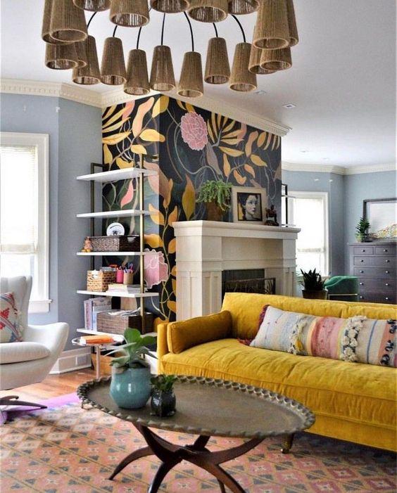 un soggiorno massimalista con camino, parete floreale, divano msutard, tavolo basso in metallo e lampadario a cono