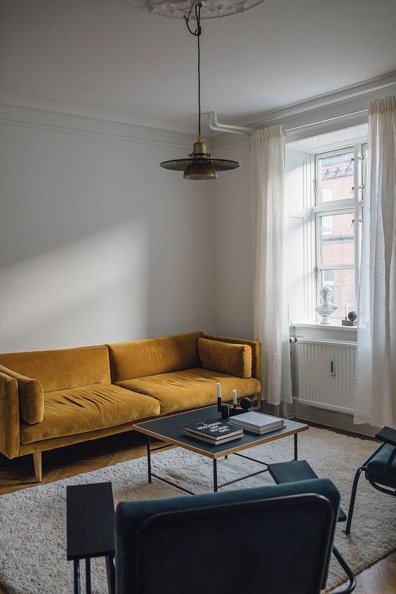 un soggiorno minimalista con un divano senape, sedie verde acqua, un tavolino basso e una lampada a sospensione retrò per una svolta