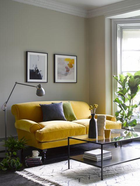 un soggiorno moderno della metà del secolo con pareti grigie, un divano vintage giallo limone, una piccola galleria a muro, un tavolo basso nero e piante in vaso