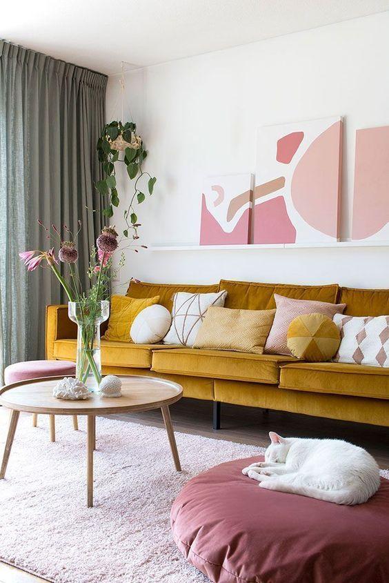 un raffinato soggiorno con un divano senape, una galleria a muro, tocchi di rosa e malva per un look molto elegante e chic