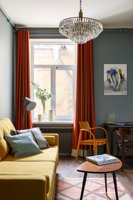 un soggiorno lunatico con pareti grigie, un divano giallo, tende color ruggine, un lampadario di cristallo e sedie e tavoli vintage