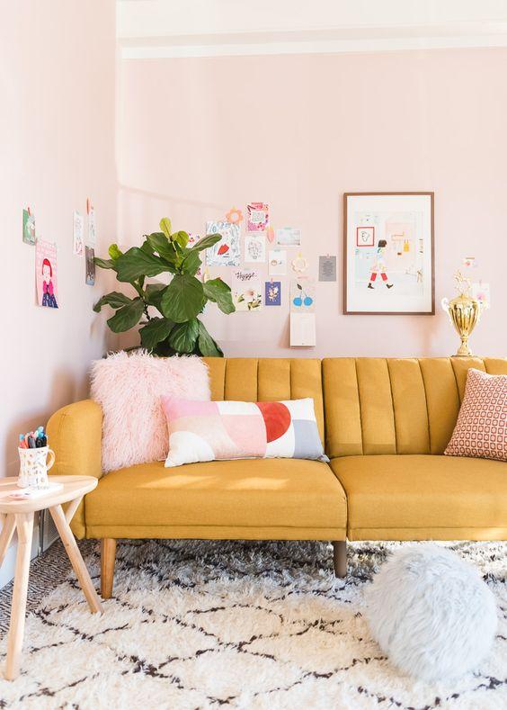 un soggiorno color pastello con un divano giallo, pareti arrossate, una parete della galleria colorata e divertente e una pianta in vaso