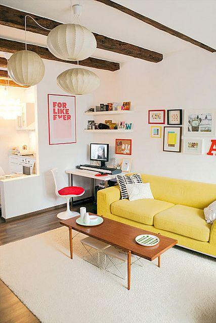un bel soggiorno bianco con travi in legno, una galleria a muro luminosa, uno spazio di lavoro e un divano giallo illuminato da lampade di carta