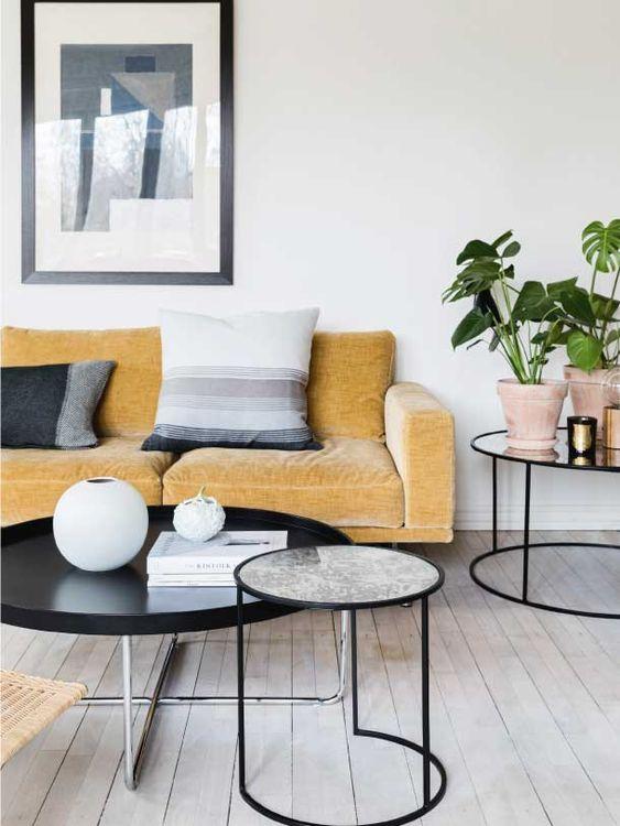 un soggiorno nordico con un divano giallo e cuscini grafici, tavoli rotondi, piante in vaso e arte grafica
