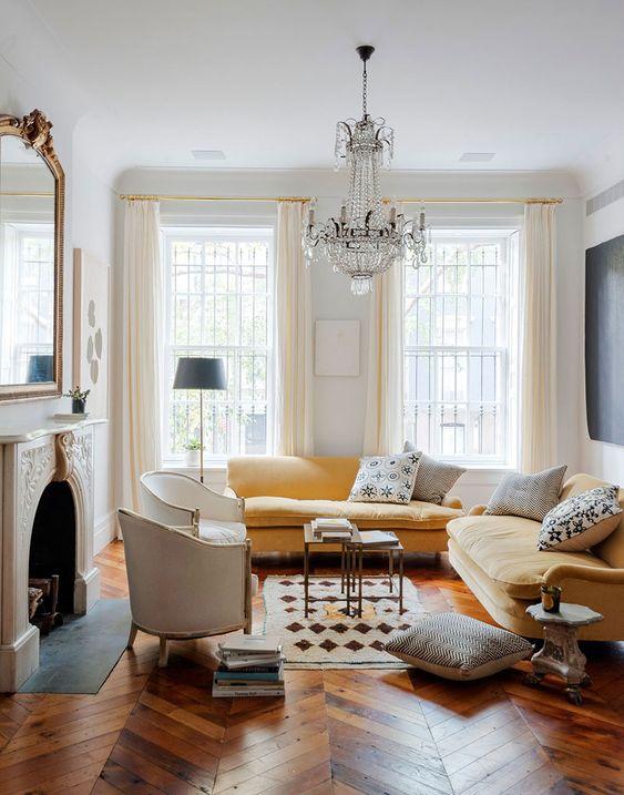 un raffinato soggiorno parigino con un camino non funzionante, un componibile giallo, un raffinato lampadario di cristallo, sedie color crema e un grande specchio sopra il camino