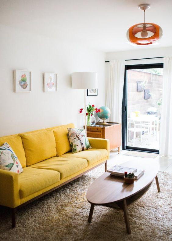 un piccolo e allegro soggiorno con un divano giallo, un tavolo ovale basso, una piccola galleria a muro e una lampada luminosa