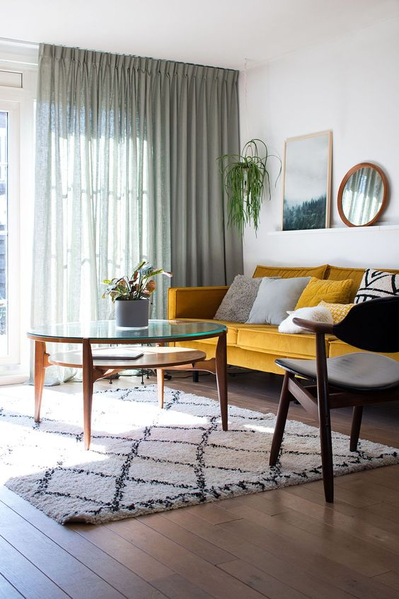 un semplice e fresco soggiorno moderno della metà del secolo con un divano giallo, cuscini grafici, una sedia e un tavolo moderni più tende verdi