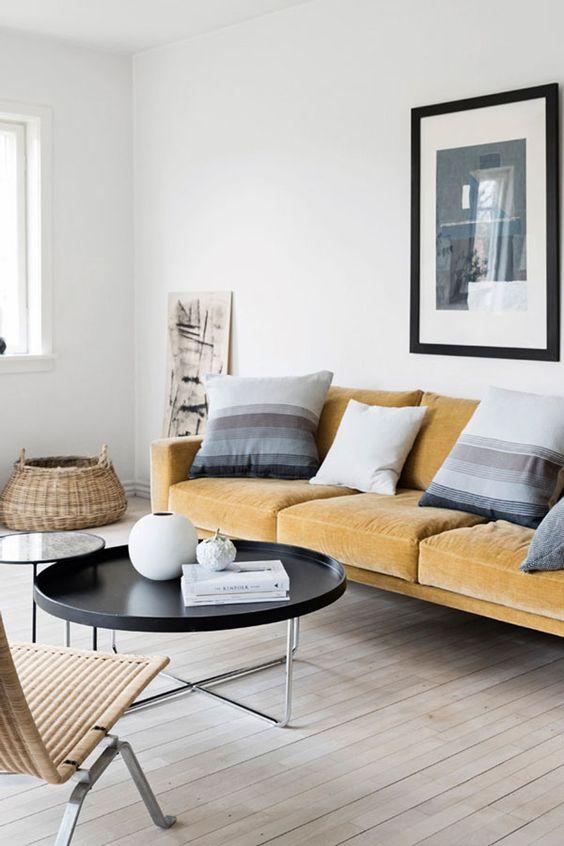 un sereno soggiorno scandinavo con un divano giallo chiaro, cuscini a righe, tavoli rotondi e un lettino in rattan è wow