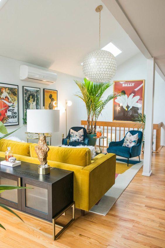un vivace spazio moderno della metà del secolo con un divano giallo e sedie blu, cuscini floreali, piante in vaso e una credenza con una lampada