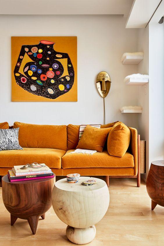 uno squisito soggiorno con un divano giallo miele, mensole galleggianti per gatti, tavoli rotondi in legno e un'opera d'arte audace