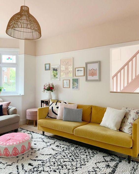 un vivace soggiorno con un divano giallo, una graziosa galleria a parete, tessuti stampati e una lampada a sospensione in rattan