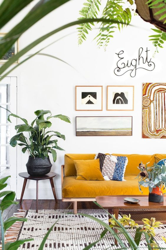 un soggiorno arioso e vivace con un divano senape, una galleria a parete, piante in vaso e un tappeto tessuto per un'atmosfera boho