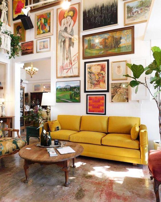 un soggiorno artistico con un'audace parete della galleria che arriva fino al soffitto, un divano giallo, un tavolo in legno vintage e una sedia stampata