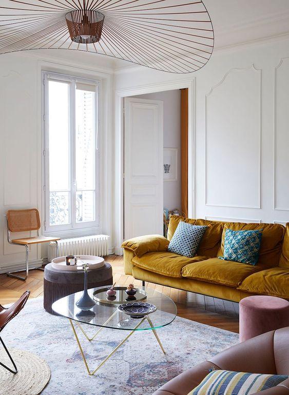 uno squisito soggiorno parigino con un divano color senape, sedie arrossate e marroni, un tavolo basso in vetro e un bellissimo lampadario