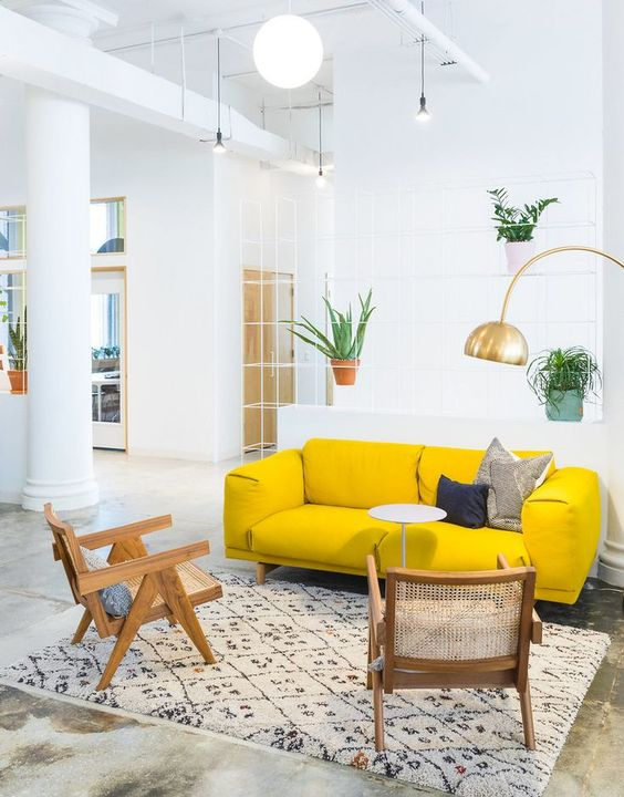 un arioso soggiorno con un divano giallo neon, sedie in rattan, una galleria d'oro e piante in vaso è sorprendente