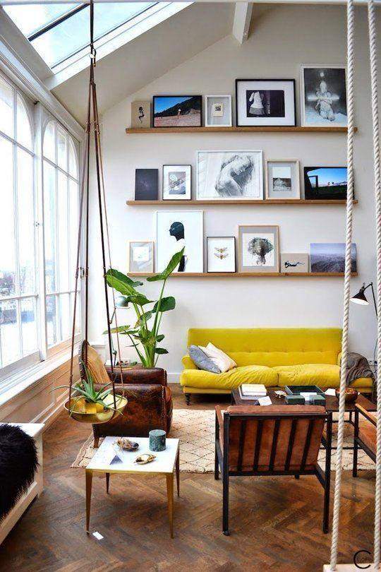 un arioso soggiorno con una parete della galleria che sale fino al soffitto, un divano giallo, sedie in pelle marrone e piante in vaso