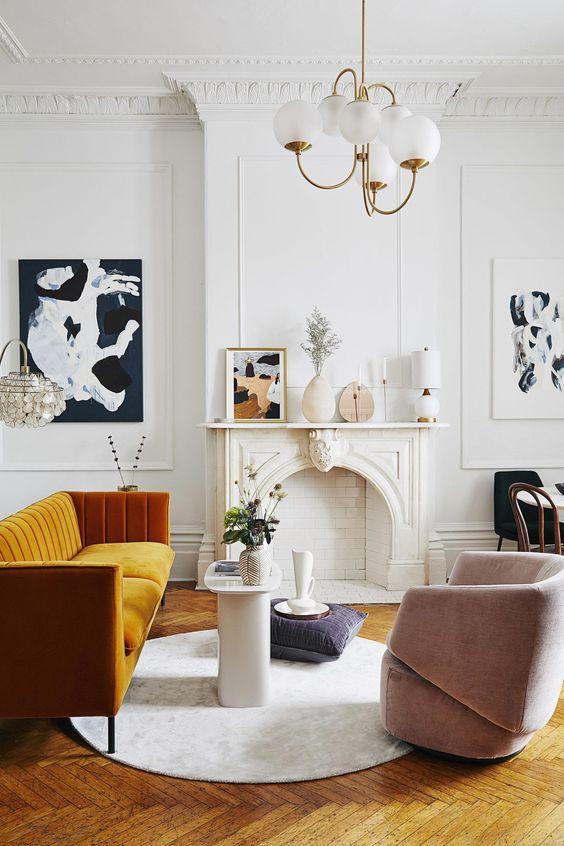 uno squisito soggiorno parigino con un camino non funzionante, un divano giallo miele, una sedia arrossata, un lampadario retrò e un'arte adorabile