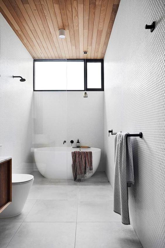 un bagno contemporaneo con penny e piastrelle di grandi dimensioni, un soffitto in legno con una finestra a lucernario e una vasca ovale