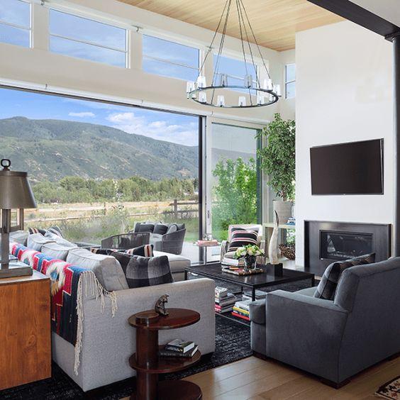 un soggiorno moderno chic con mobili comodi e un camino incorporato, una parete vetrata e finestre a lucernario aggiuntive per riempire lo spazio di luce