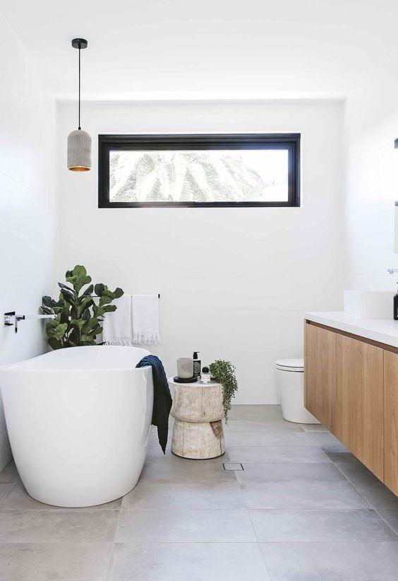 un bagno moderno con un lavabo sospeso, una vasca ovale, una lampada a sospensione e una finestra a lucernario più un po 'di verde