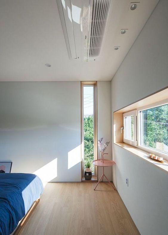 una camera da letto contemporanea con una finestra lunga e stretta e una a lucernario, con biancheria da letto blu è chic