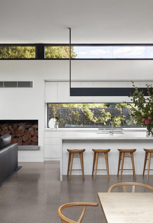 uno spazio bianco contemporaneo con una lunga finestra come alzatina e finestre a lucernario più mobili contemporanei