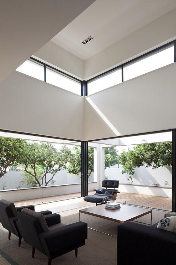 uno spazio contemporaneo in bianco e nero con pareti da rimuovere e finestre a lucernario che portano più luce a questo spazio del soffitto a doppia altezza
