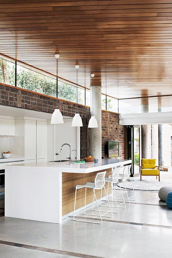 uno spazio contemporaneo con un muro di mattoni, mobili bianchi eleganti, lampade a sospensione e finestre a lucernario che illuminano