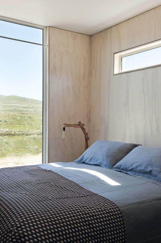 una camera da letto contemporanea con pareti in legno biondo, un letto comodo, una parete vetrata e una finestra a lucernario per ulteriore luce
