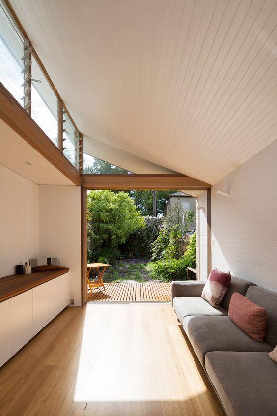 un soggiorno contemporaneo con un divano grigio, una credenza minimalista, una parete vetrata e finestre a lucernario per la luce naturale all'interno
