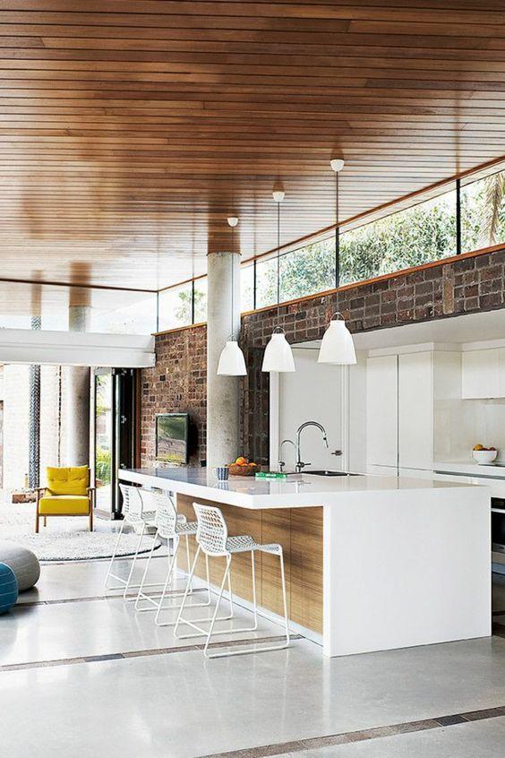 una cucina moderna della metà del secolo con un muro di mattoni, mobili bianchi minimalisti e finestre a lucernario che portano alla luce