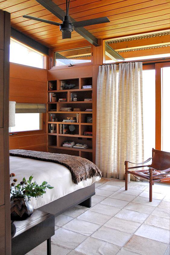 un'accogliente camera da letto moderna della metà del secolo con uno scaffale incorporato, un letto e una sedia in pelle e alcune finestre a lucernario