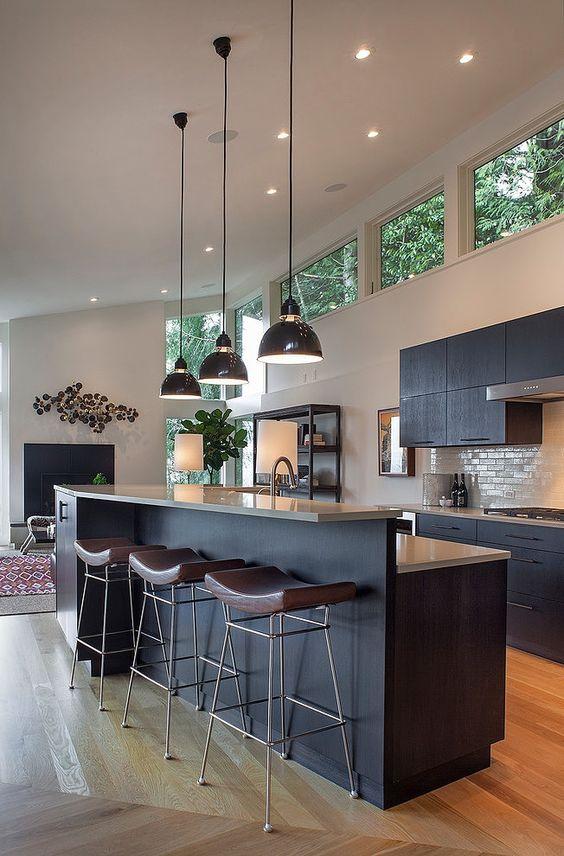 una cucina moderna della metà del secolo con mobili neri, finestre a lucernario per più luce, lampade a sospensione e sedie in pelle