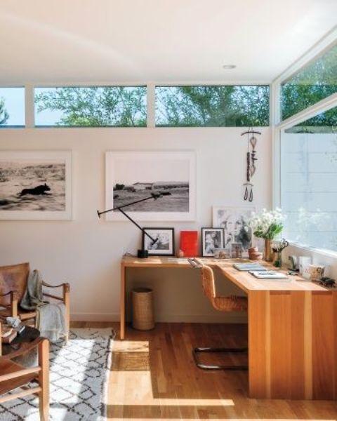 un ufficio domestico moderno della metà del secolo con pareti vetrate e finestre a lucernario, una scrivania ad angolo e sedie in pelle è accogliente