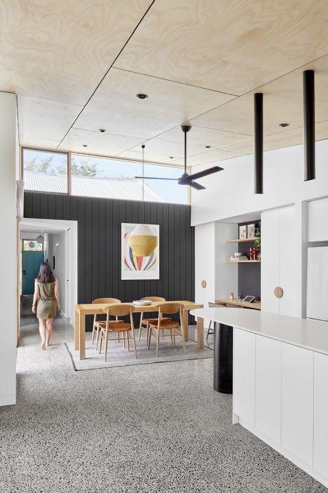una cucina moderna della metà del secolo e una zona pranzo con mobili chic, finestre a lucernario per più luce e luci a sospensione fresche