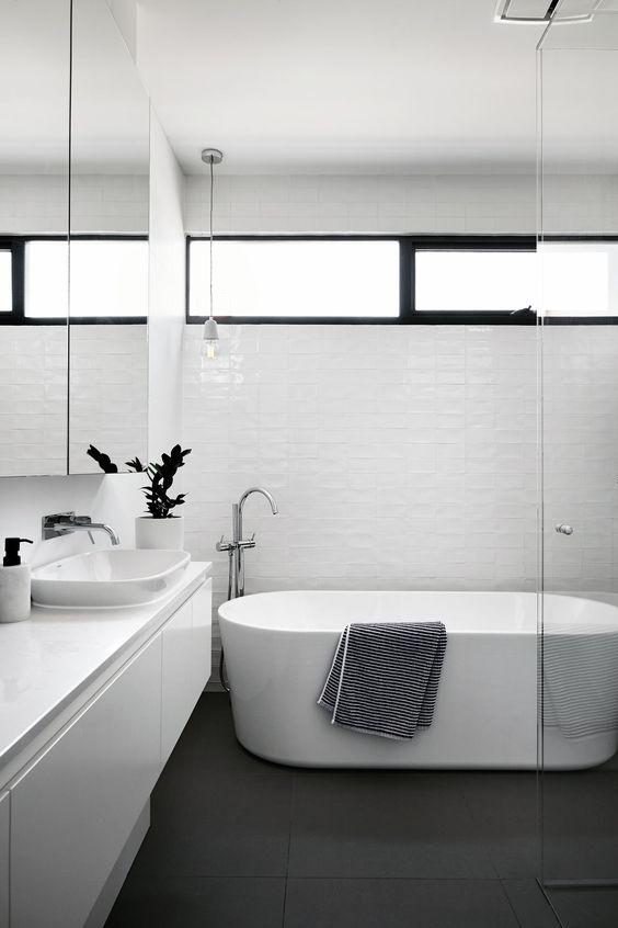 un bagno minimalista con piastrelle ed elettrodomestici bianchi, una finestra a lucernario per luce ma allo stesso tempo abbastanza privacy