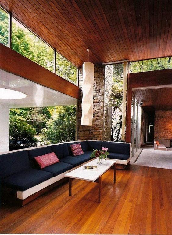 un moderno soggiorno della metà del secolo con un ampio sezionale, un tavolino da caffè e finestre a lucernario e una parete vetrata