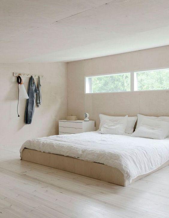 una camera da letto minimalista in tonalità chiare, con un comò e un letto più finestre a lucernario per più luce