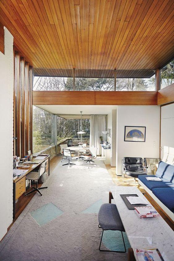 uno spazio moderno della metà del secolo con mobili colorati, pareti vetrate e finestre a lucernario oltre a un soffitto rivestito in legno