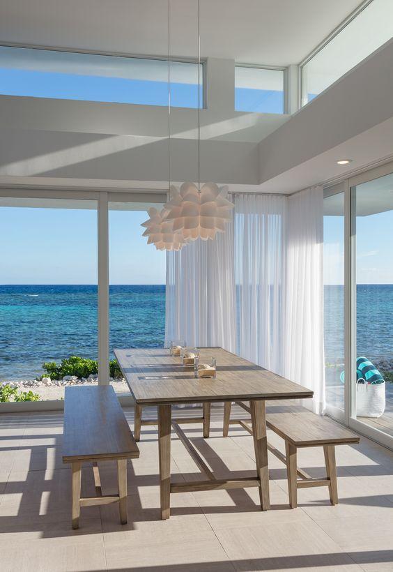 una moderna casa sulla spiaggia in bianco, con mobili in legno, lampade a sospensione e pareti vetrate più finestre a lucernario